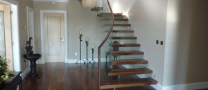 Curved, walnut finish cantilever glass stairs